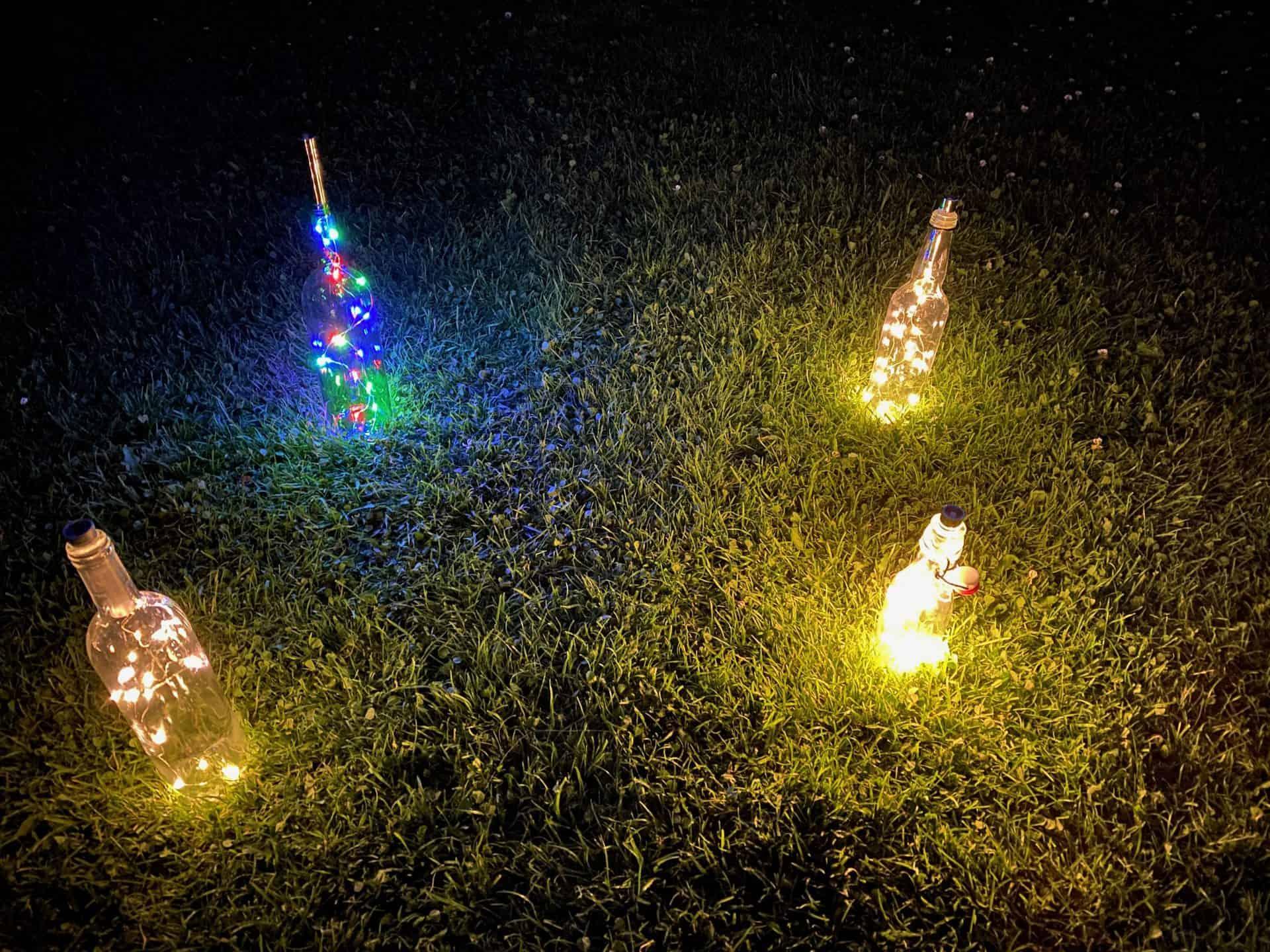 Gemütliches-Flaschenlicht-Bügelflasche-LED-warmweiss-bunt-von-der-Seite-in-der-Wiese